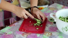 Ukrainian Girl Housewife is Cutting Cucumbers on Salad in Apron Stock Footage