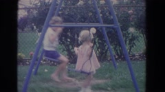 1965: two children playing on blue swingset and pushing each other on summer day Stock Footage