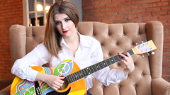 Girl in a white shirt plays guitar in hippie style Stock Footage