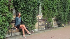 Slender young brunette is sitting on a bench, looking around and smiling Stock Footage