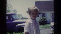 1965: a old video of a little girl in her neighborhood smiling at the camera Stock Footage