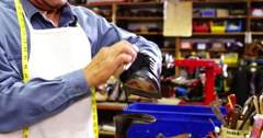 Smiling cobbler polishing a shoe Stock Footage