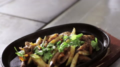Shot of fryed vegetables with meat in hot pan on wooden stand Stock Footage