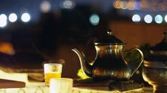 Traditional Metal Pot and Glasses With Steaming Moroccan Tea on the Night City Stock Footage