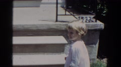 1965: small child walks up stoop opens the screen door, turns and smiles Stock Footage
