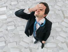 Businessman has headache. Disappointment and failure concept. A lot of docume Stock Photos