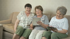 Elderly women look at photos on screen of tablets Stock Footage