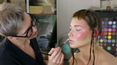 Stylist to apply makeup on the model's face Stock Footage
