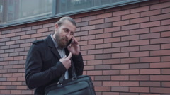 Distracted businessman pulling out his mobile Stock Footage