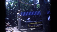 1958: a uniformed man lets one of several birds out of an outdoor cage. FLORIDA Stock Footage