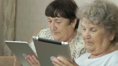 Two elderly sisters holding silver digital tablets Stock Footage