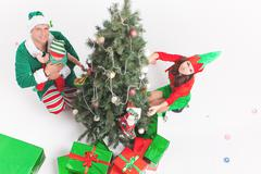 Happy family decorating Christmas tree, dressed in elf costumes Stock Photos