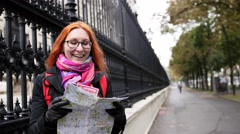 Yong woman tourist with red hair and glasses looking map in Vienna near Neue Stock Footage