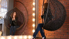 Girl in a leather jacket preening before the mirror in a designer chair Stock Footage