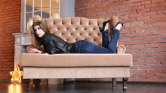 Charming slim girl in a leather jacket with high pumps lying on a sofa Stock Footage