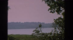 1959: grainy footage from the bank of a tree-lined river, as a light breeze Stock Footage