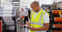 4K Young business manager in printing factory looking down at paperwork Stock Footage