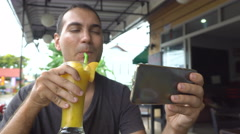 Caucasian man drink fruit shake and chat on mobile phone Stock Footage