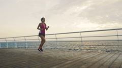 Active brunette wearing stylish sport clothes running on beautiful beach in Stock Footage