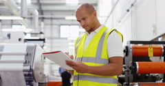 4K Portrait smiling worker in a printing factory looking at paperwork Stock Footage