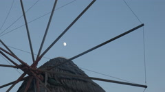 The moon and a close up of the historic windmills on mykonos, greece Stock Footage