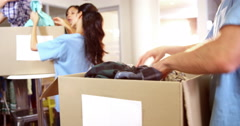 Male volunteer packing clothes in donation box Stock Footage
