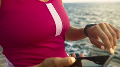 Serious young active woman checking miles on her fitness tracker Stock Footage