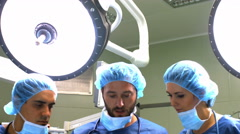 Male and female surgeons discussing over digital tablet in operation room Stock Footage