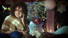 4k Christmas and New Year Holiday Woman Talking on Phone at Fireplace Stock Footage