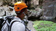 Backpacker man hiking and taking pictures of waterfall in Barranco del Infier Stock Footage