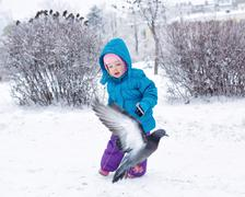Cute little girl chasing pigeons Stock Photos