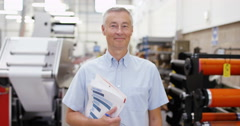 4K Portrait smiling business owner in print factory with machinery in background Stock Footage