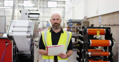 4K Portrait successful business owner in print factory, machinery in background Stock Footage