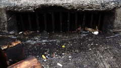 Water from heavy rain flows into drain beside the street, slow motion Arkistovideo