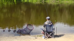 Fisher man is fishing on the bank of the river, the lake on the feeder tackle Stock Footage