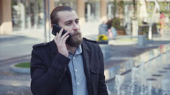 Handsome bearded man talking phone in city Stock Footage