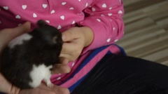 Mother holding a hamster in hands, daughter  feed him with carrots Stock Footage