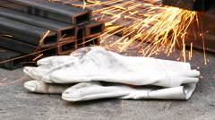 Worker's gloves and splashes of sparks in the workshop Stock Footage