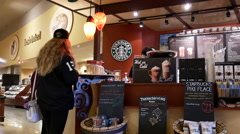 Close up woman waiting for her coffee inside Starbucks store Stock Footage