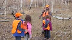A hunter with his children walks through woods Stock Footage