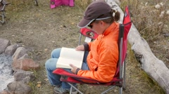 A woman reads a book while camping outside Stock Footage
