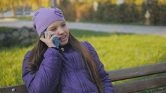 Beautiful teen girl smiling and talking on the phone in autumn park. dental Stock Footage