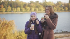 Mom and daughter in the park drinking coffee and cocoa with marmalade Stock Footage
