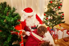 In Christmas Santa Claus distributes gifts to children out of the bag in the  Stock Photos