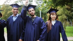 Happy students in mortar boards with diplomas Stock Footage