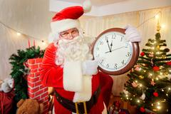 Santa Claus holding a watch in his hand, pointing at the clock at five minute Stock Photos