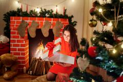 The beautiful Christmas girl in red dress near the fireplace,  tree with a gi Stock Photos