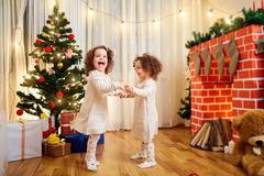 Little girls twins children Christmas dancing, having fun, laughing in the ro Kuvituskuvat