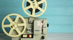 Old vintage movie projector on a blue wooden background Stock Footage