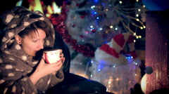 4k Christmas and New Year Holiday Girl in Rob Drinking Coffee at Fireplace Stock Footage